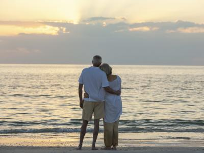 elderly couple hugging on beach after getting estate planning advice sunshine coast